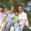 Family having fun on spinning roundabout - Stock Photo