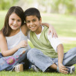 Two children sitting in park — Stock Photo