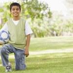 Boy in park holding football — Stock Photo