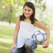 Girl holding football in park — Stock Photo