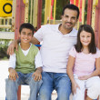 Stock Photo: Father with children in playground