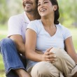 Couple relaxing in park - Stock Photo