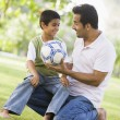 Foto Stock: Father and son playing football