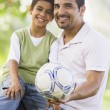 Stock Photo: Father and son playing football together