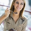 Woman eating chocolate cake in cafe — Stock Photo