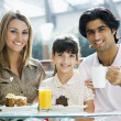 Family eating cake in cafe — Stock Photo