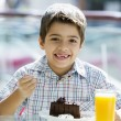 Young boy eating chocolate cake in cafe — Stock Photo