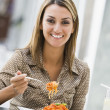 Stock Photo: Woman eating pasta at cafe