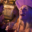 Young woman in cowboy hat laughing at a nightclub - Lizenzfreies Foto