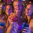 Three young women with drinks in nightclub — Stock Photo #4760952