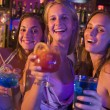 Stock Photo: Three young women with drinks in nightclub