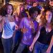 Young men and women dancing in a nightclub — Foto Stock