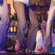 Barman gaping at three young women dancing on bar counter - Stock Photo