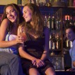Two young women sitting on a bar counter, enjoying cocktails — Stock Photo #4760974