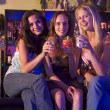 Three young women sitting on a bar counter, enjoying cocktails — Stock Photo #4760976