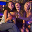 Three young women sitting on a bar counter, toasting the camera — Stok fotoğraf