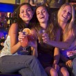 Three young women sitting on a bar counter, toasting the camera — Stock Photo