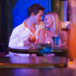 Happy young couple sitting in a nightclub, smiling at each other — Стоковая фотография
