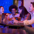 Stock Photo: Group of young adults in a nightclub talking and laughing