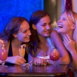 Three young women sitting at a table and laughing in a nightclub — Stock Photo #4760990