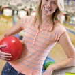 Young woman holding a bowling ball in a bowling alley - Stock Photo