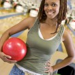 Young woman holding a bowling ball in a bowling alley — Stock Photo