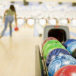 Bowling ball machine with woman bowling in the background — Stock Photo