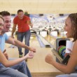 Four young adults cheering in bowling alley — Stock Photo #4761011