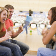 Young adults cheering in a bowling alley — Stock Photo