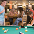 Stock Photo: Two young men playing pool at bar