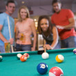 Young couples playing pool in a bar (focus on pool table) - Stock Photo
