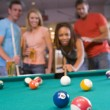Stock Photo: Young couples playing pool in bar (focus on pool table)