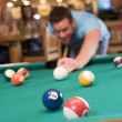 Young man playing pool in a bar (focus on pool table) — Stock Photo