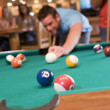 Stock Photo: Young mplaying pool in bar (focus on pool table)