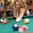 Young woman playing pool in a bar - Stock Photo