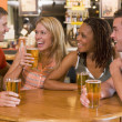 Foto Stock: Group of young friends drinking and laughing in bar