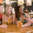 Group of young friends drinking and laughing in a bar — Stock Photo