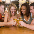 Foto Stock: Group of young friends toasting in a bar