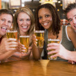 Group of young friends in bar toasting the camera — Stock Photo