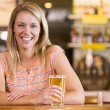 Young woman enjoying a beer at a bar — Stock Photo #4761033