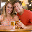 Happy young couple having beers at a bar — Zdjęcie stockowe #4761035