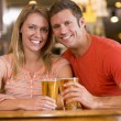 Foto Stock: Happy young couple having beers at a bar