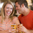 Young man in bar whispering into his girlfriends's ear — Stock Photo