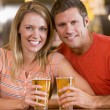 Happy young couple having beers at a bar — Stock Photo