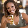 Young woman relaxing with a beer at a bar — Stock Photo