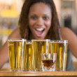 ������, ������: Young woman staring excitedly at a round of beers