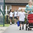 A woman with a pushchair walking her son home from school - Stock Photo