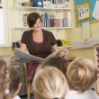 A teacher reads to schoolchildren in a primary class - Stock Photo