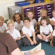 Stock Photo: Teacher reads to schoolchildren in primary class