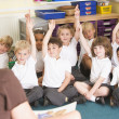 Schoolchildren raise their hand in a primary class - Stock Photo